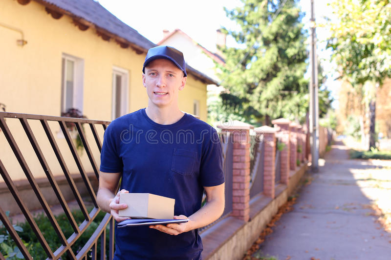 Man Courier Brings Order Smiling at Camera on Background of Tree royalty free stock photography