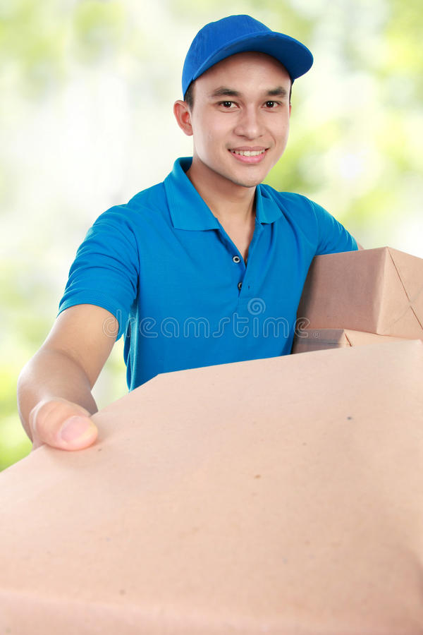 Man courier with packages. Young man courier in blue uniform giving a package stock images