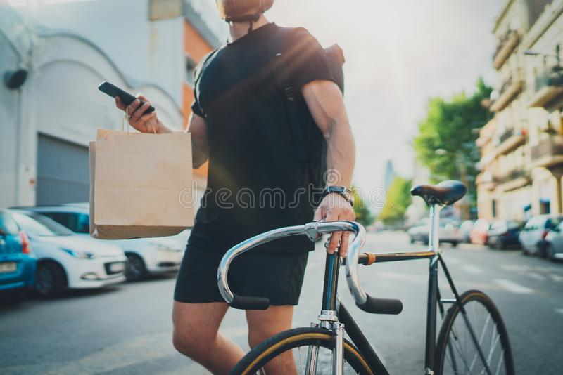 Man courier using a map app on mobile phone to find the delivery address in the city. Anonimous Courier delivery food. Service at home royalty free stock photography