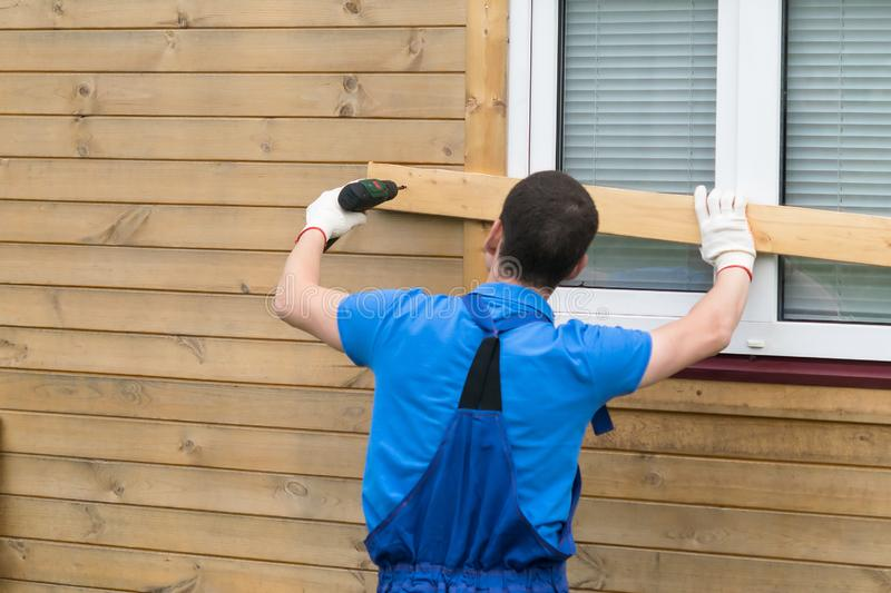 Man in coveralls closes windows with boards to protect the house. Man in coveralls closes  windows with boards to protect the house royalty free stock photo