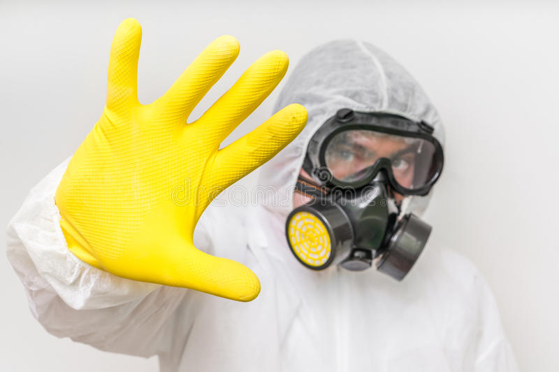 Man in coveralls with gas mask is showing stop gesture. Ecology and pollution concept stock image