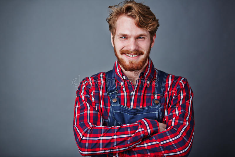 Man in coveralls. Handsome guy in coveralls looking at camera with smile stock photo