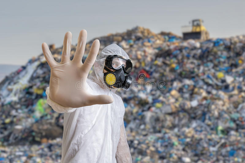 Man in coveralls is showing stop gesture. Garbage pile in landfill in background.  stock images