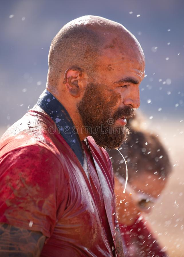 Man covered with mud splatters and dripping water while washing off after a mud run royalty free stock image