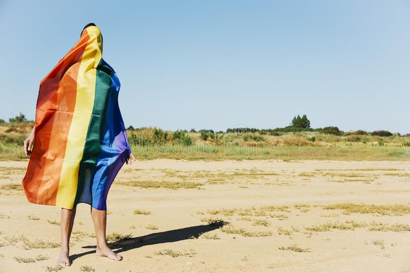 Man covered with a rainbow flag stock photo