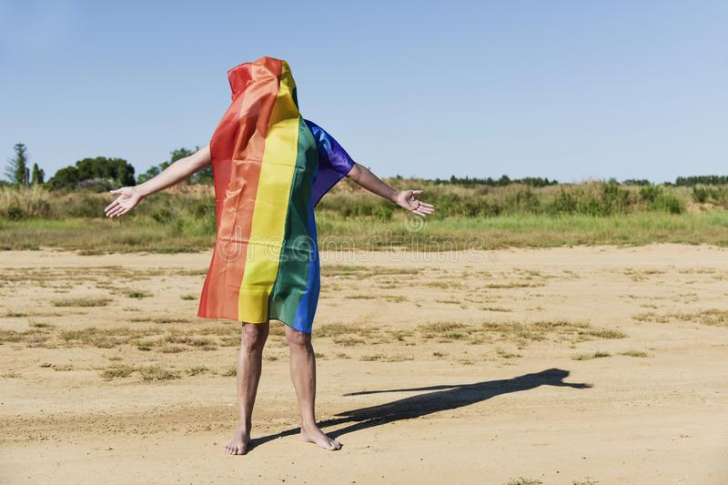 Man covered with a rainbow flag. A barefoot young caucasian man covered with a rainbow flag standing in a natural landscape royalty free stock image