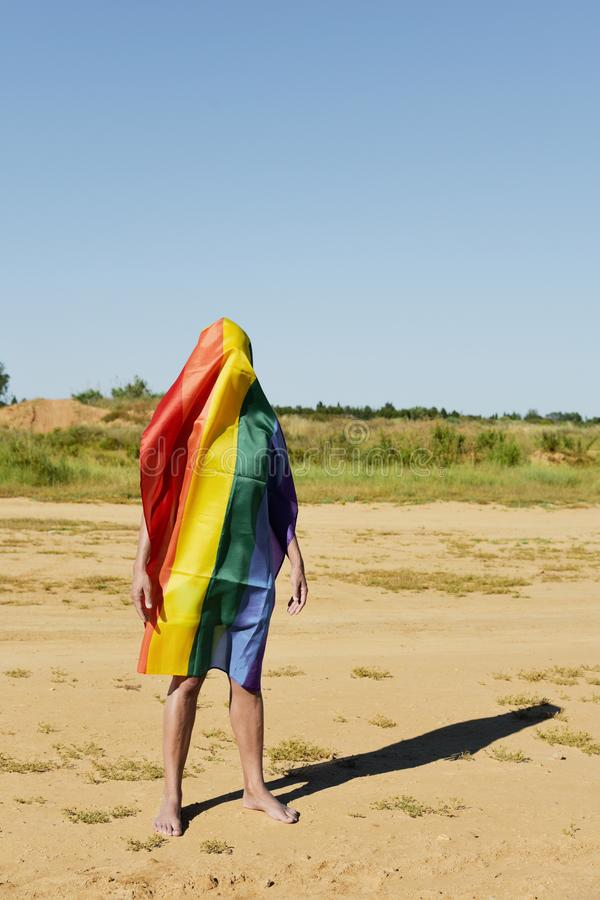 Man covered with a rainbow flag. A barefoot young caucasian man covered with a rainbow flag standing in a natural landscape royalty free stock photography