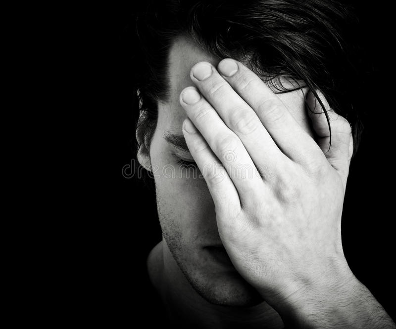 Man covering face with hand. Depressed man or person with headache covering face with hand, black and white portrait with studio background and copy space stock images