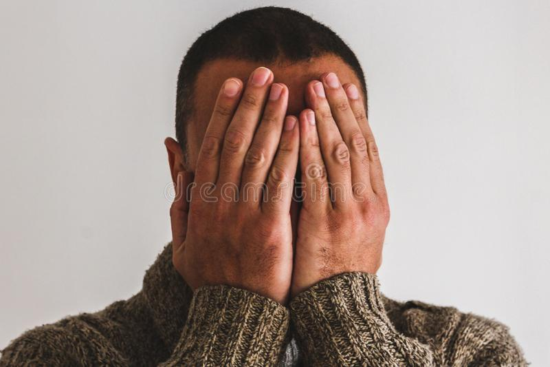 A man covering is face stock photos