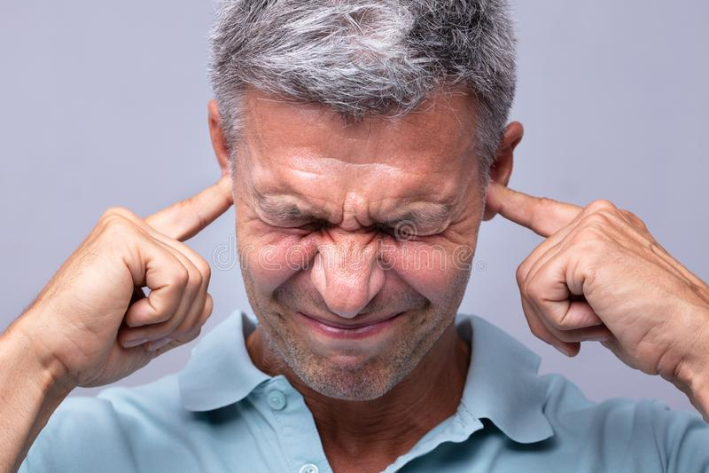Man Covering His Ears With Fingers royalty free stock photos