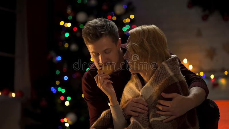 Man covering lady with plaid, playfully biting cookie, romantic Christmas night royalty free stock image
