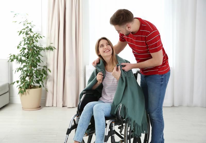 Man covering woman in wheelchair with plaid. Helping disabled. Man covering women in wheelchair with plaid at home. Helping disabled royalty free stock images