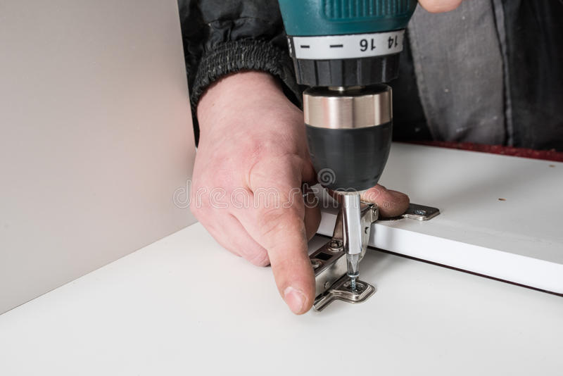Man covers Furniture loops. Screwing the furniture hinge leaf to the white cabinet in the small wholesale furniture company stock photography