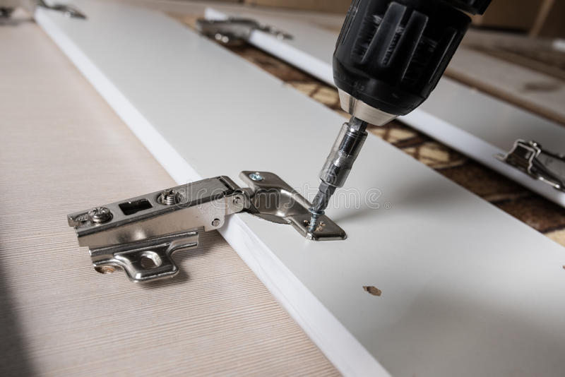 Man covers Furniture loops. Screwing the furniture hinge leaf to the white cabinet in the small wholesale furniture company royalty free stock photography