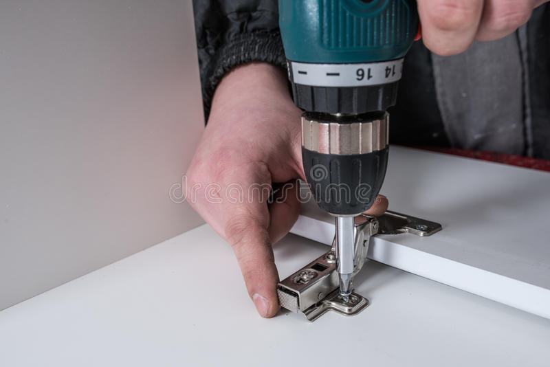 Man covers Furniture loops. Screwing the furniture hinge leaf to the white cabinet in the small wholesale furniture company royalty free stock photos