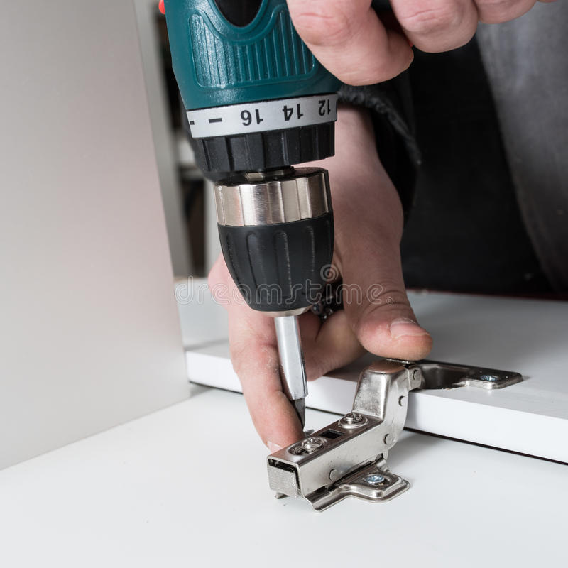 Man covers Furniture loops. Screwing the furniture hinge leaf to the white cabinet in the small wholesale furniture company stock image