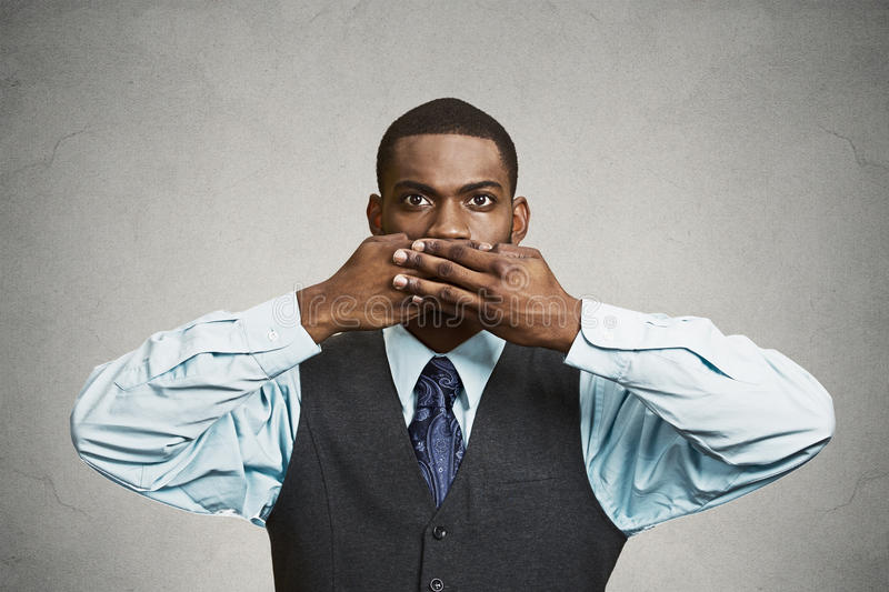 Man covers his mouth, speak no evil concept. Closeup portrait, silent young business man covering closed mouth observing. Speak no evil concept, black background stock image
