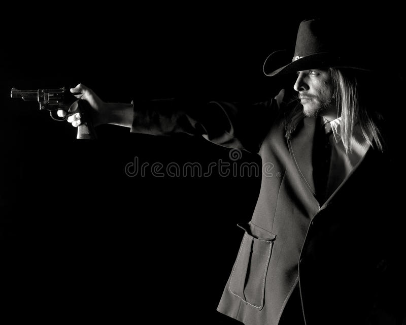 Man in Cowboy Hat Aiming pistol. stock photo