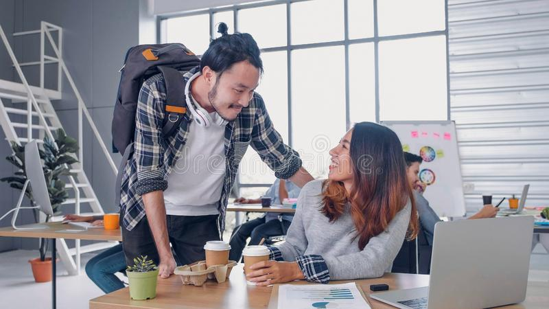 Man creative designer buy coffee cup to woman colleague at modern office in morning at desk.casual workplace lifestyle. Man creative designer buy coffee cup to royalty free stock image