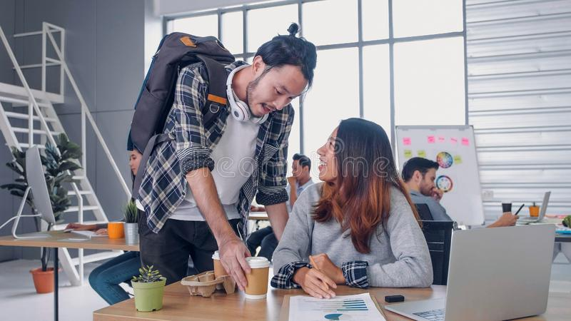 Man creative designer buy coffee cup to woman colleague at modern office in morning at desk.casual workplace lifestyle. Man creative designer buy coffee cup to stock photography