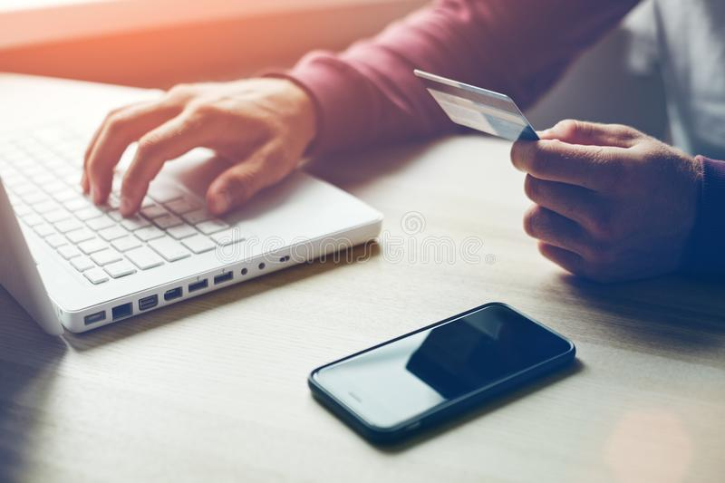 Man with credit card in hand and smartphone using laptop. Online payment royalty free stock photo