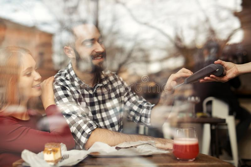 Man with credit card using payment terminal at restaurant. View through window royalty free stock photos