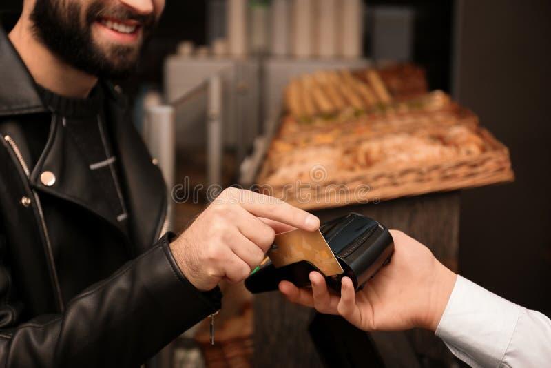 Man with credit card using payment terminal at shop. Closeup stock photography