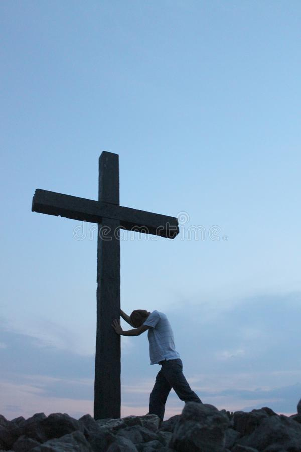 Man at the cross 1. Young man leaning against a cross in posture of helplessness royalty free stock photos