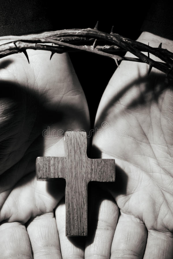 Man with a cross and a crown of thorns. Closeup of the open hands of a young caucasian man with a small wooden cross and a crown of thorns, in black and white stock photos
