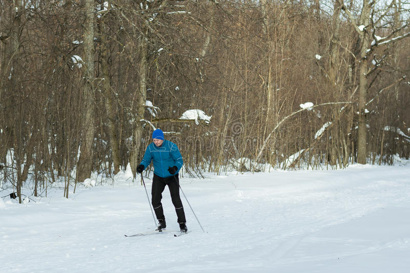 The man on the crosscountry skiing in winter forest. Ice ridge course skiing. Healthy lifestyle concept stock photo