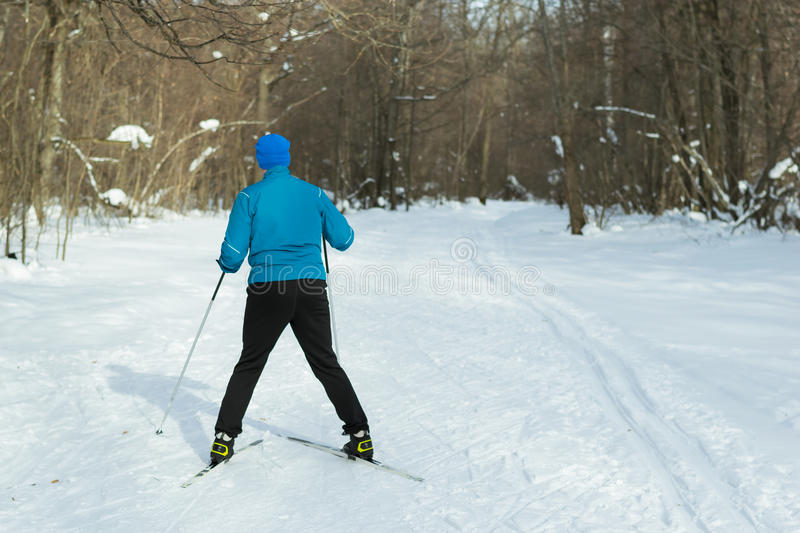 The man on the crosscountry skiing in winter forest. Ice ridge course skiing. Healthy lifestyle concept stock photos