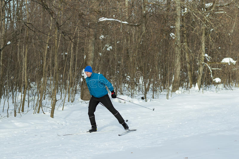 The man on the crosscountry skiing in winter forest. Ice ridge course skiing. Healthy lifestyle concept stock photography