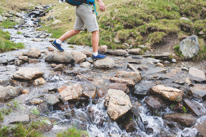 Man crossing a river on stones royalty free stock photography