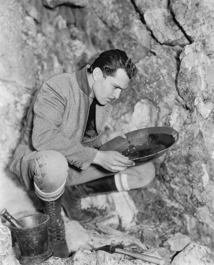 Man crouching and panning for gold stock image