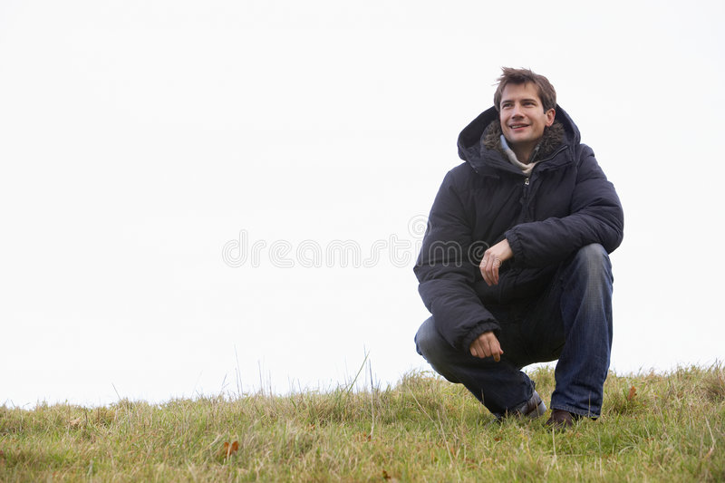 Man Crouching In Park Royalty Free Stock Image