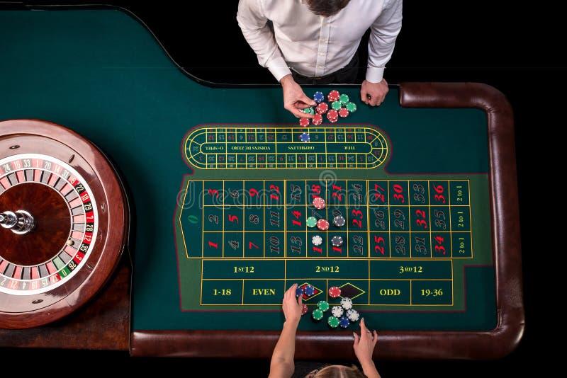 Man croupier och kvinnan som spelar rouletten på tabellen i kasinot Bästa sikt på en grön tabell för roulett med ett band arkivbilder