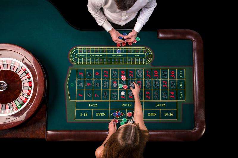Man croupier and woman playing roulette at the table in the casino. Top view at a roulette green table with a tape. Man croupier and women playing roulette at stock photo
