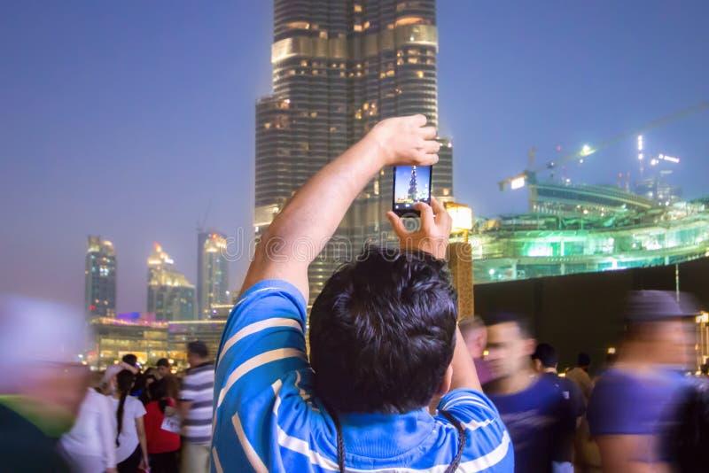 A man in the crowd photographs the Dubai skyline. DUBAI, UNITED ARAB EMIRATES - 28 Ott, 2016: Outside the Dubai Mall. People photographing the Burj Khalifa, the