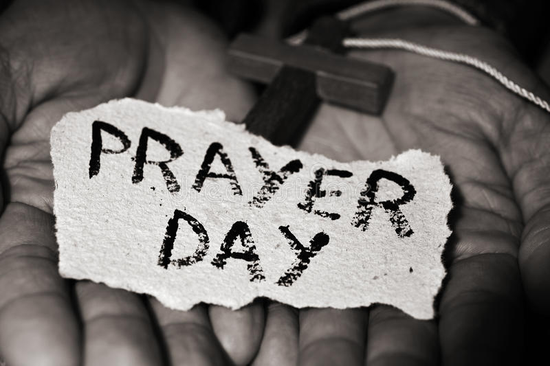 Man with crucifix and text prayer day. Closeup of the hands of a young caucasian man with a wooden crucifix and a piece of paper with the text prayer day in them stock photography