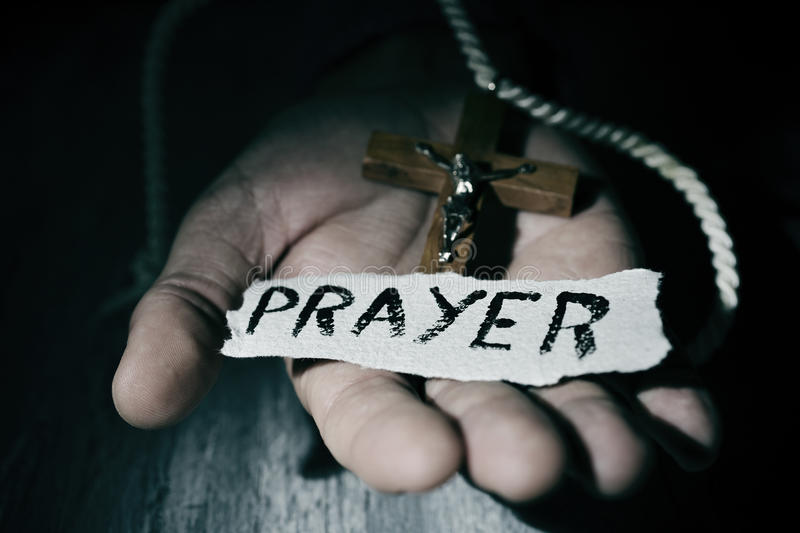 Man with crucifix and word prayer. Closeup of the palm of a young caucasian man with a wooden crucifix and a piece of paper with the word prayer day in it royalty free stock images