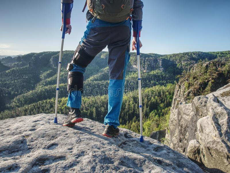 Man with crutches and strong will. Disabled tourist climb stock photography
