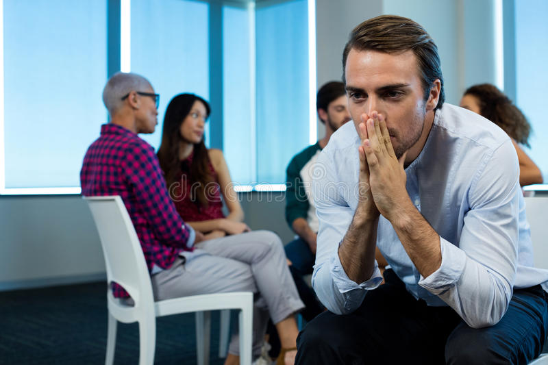 Man crying while creative business team in background royalty free stock photos