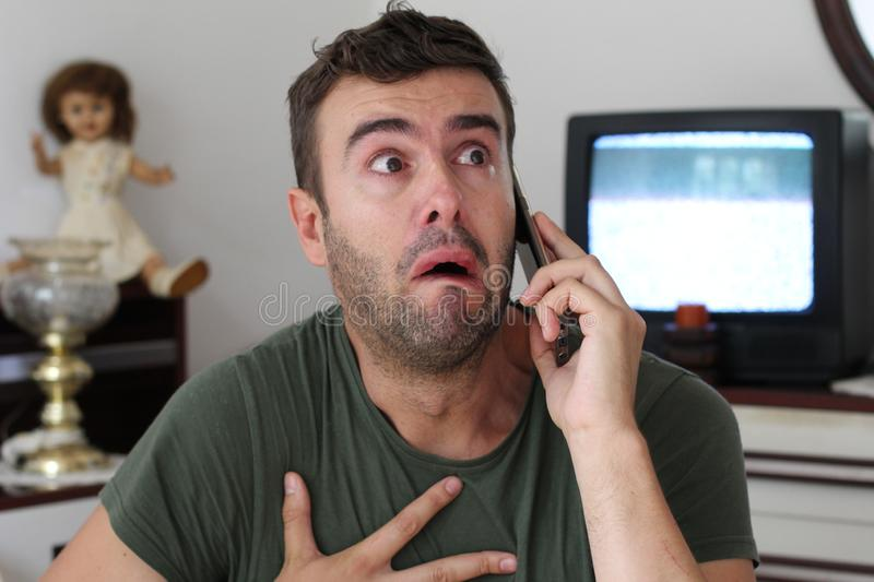 Man crying at home during phone conversation royalty free stock images