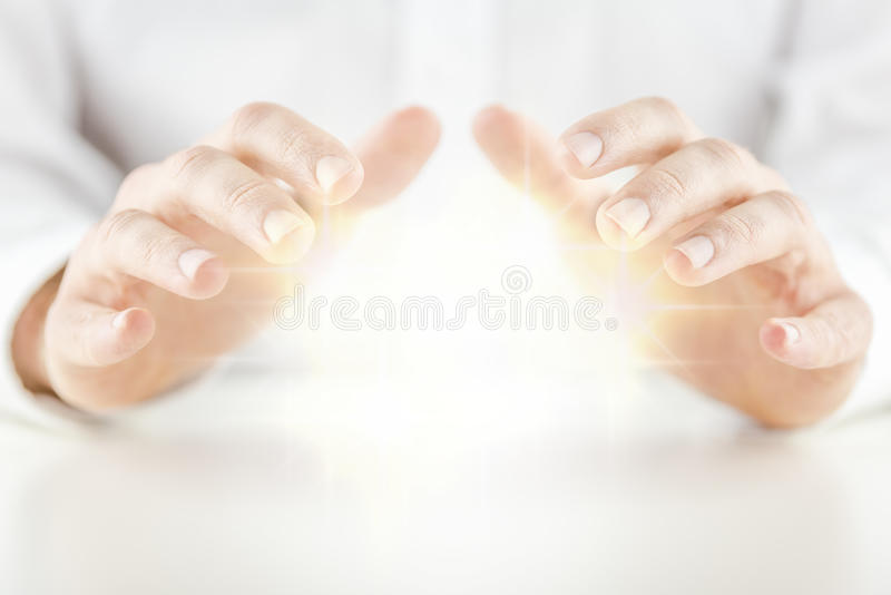 Man with a crystal ball. Man with a glowing crystal ball holding his hands protectively above it to feel the energy as he foretells or predicts the future