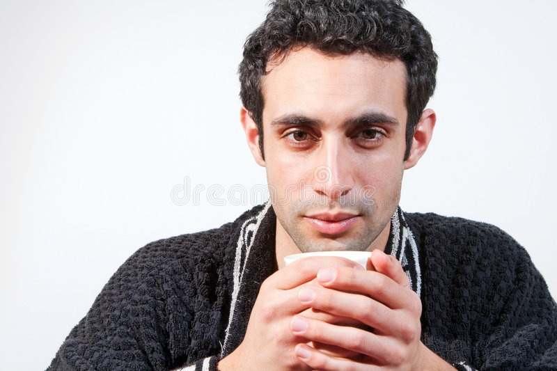 Man with cup. Tired handsome man with a mug wearing a black robe, isolated royalty free stock images
