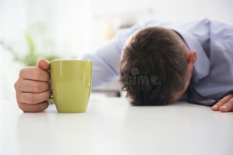 Man with cup of drink sleeping at home in morning stock photography