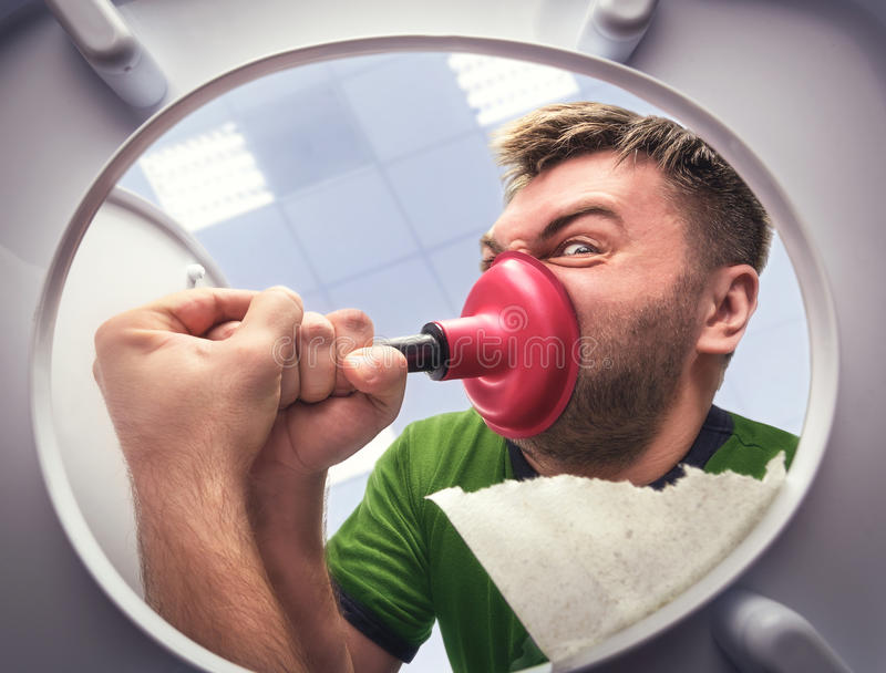 Man with cup plunger. Man cleaning the toilet with cup plunger stock photography