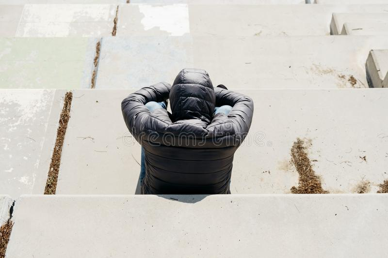 Man curled up sitting on an outdoor stairway. A young caucasian man, seen from behind, wearing jeans and a gray hooded jacket, curled up sitting on an outdoor royalty free stock photo