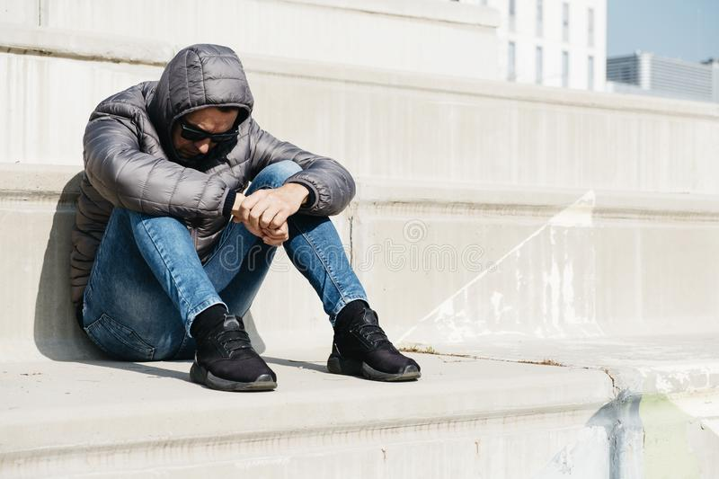 Man curled up sitting on an outdoor stairway. A young caucasian man, wearing jeans and a gray hooded jacket, curled up sitting on an outdoor stairway stock images