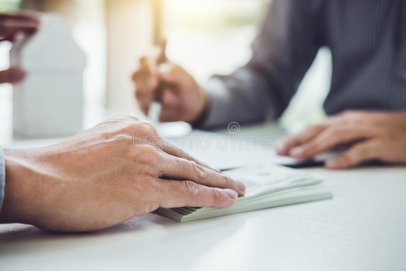 Man customer signing buying home policy document agreement, successful loan contract and salesman receive money after good deal.  royalty free stock images